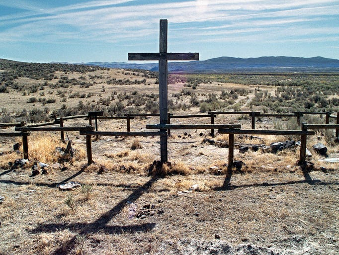"A huge cross marks the graveyard containing the remains of pioneers killed by Indians in the Gravelly Ford area near Beowawe in Eureka County.  Photo from the  book ""Alkali Angels"""