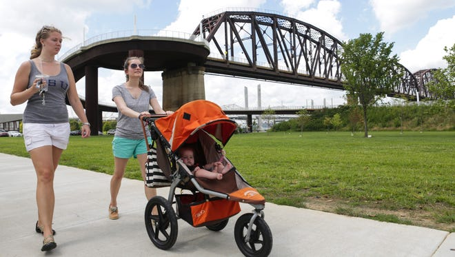 """Candice Lofton, from left, walks with friend Kate Cope and her daughter Allie Cope near the Big Four Pedestrian Bridge Thursday. Cope and Lofton both enjoy visiting the bridge with family and pets to get outside for exercise, but aren't happy to hear that soon they may be charged for parking. """"If they were to start charging for parking that would definitely curtail our ability to come,"""" Lofton said. """"Part of the attraction is that it's free and it's accessible to everyone."""" Cope echoed Lofton in her sentiments. """"If they start charging I'm not sure I would continue to come here,"""" Cope said. """"Three hours seems like more time than I usually spend, so I'm not sure I'd be willing to pay three dollars."""" Aug. 24, 2016"""