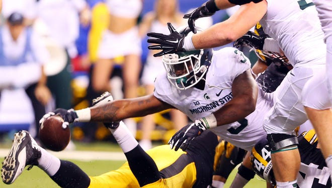 Michigan State Spartans running back LJ Scott (3) dives in for a touchdown during the fourth quarter of the Big Ten Conference football championship game against the Iowa Hawkeyes at Lucas Oil Stadium.