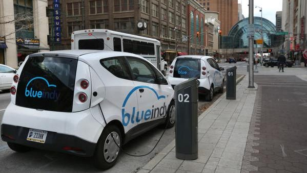 Five demonstration models of BlueIndy electric cars are parked at the company's charging stations in downtown Indianapolis.