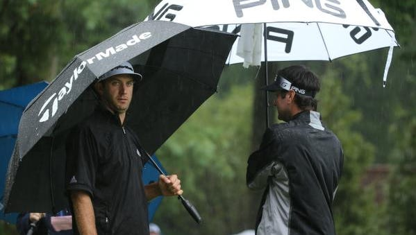 Dustin Johnson, left, talks with Bubba Watson, right, as they wait after play was suspended during the second round of the PGA Championship golf tournament at Baltusrol Golf Club in Springfield, N.J., Friday, July 29, 2016. (AP Photo/Seth Wenig)