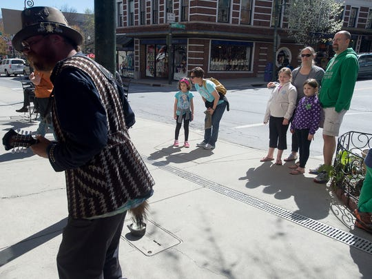 Families stop to watch and listen to a band playing on Haywood Street Tuesday March 29, 2016 in downtown Asheville.