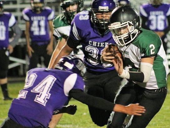 Cloudcroft's Dylan Eldridge throws a stiff arm toward