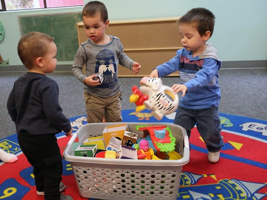From left, Jovi Haswell, 1, Richie Haswell, 2, and Kamdyn Wheeler, 2, put away toys at the Holly Ridge Center on Friday. The center, devoted to helping people with developmental disabilities, is acquiring a new building on Kitsap Way in Bremerton to go with its existing facility on Taylor Road in Chico.