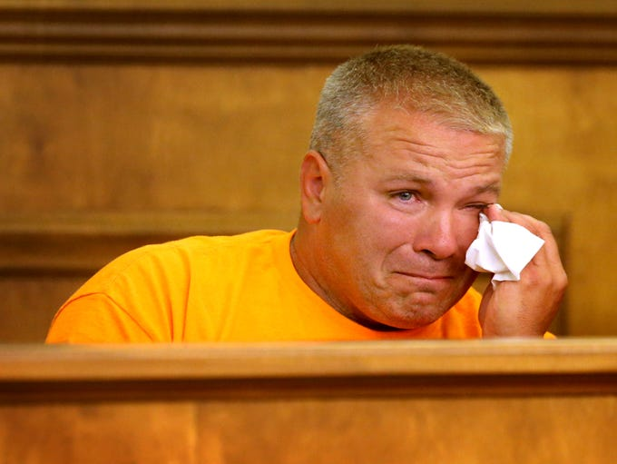 Michael Bess wipes away tears while on the witness