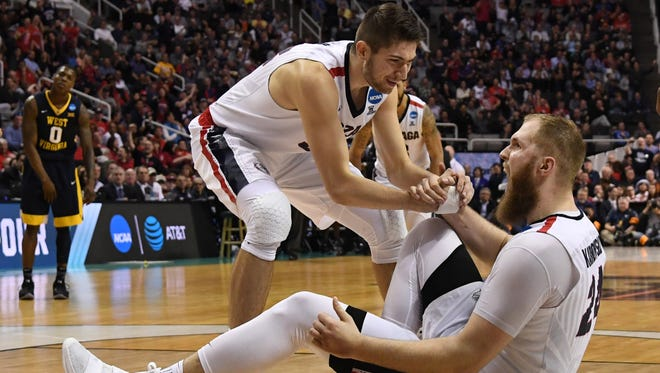Gonzaga Bulldogs center Przemek Karnowski (24) celebrates as he is helped up by forward Zach Collins (32) during the second half in the semifinals of the West Regional of the 2017 NCAA Tournament against the West Virginia Mountaineers at SAP Center.