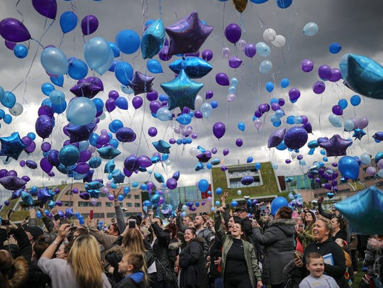 People react as balloons are released in memory of