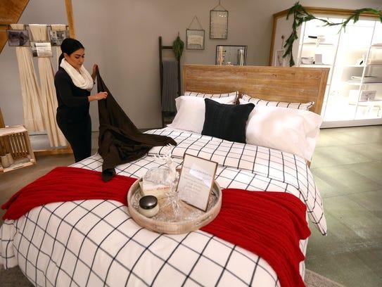 General Manager Kelsey McKinnon arranges bedding at