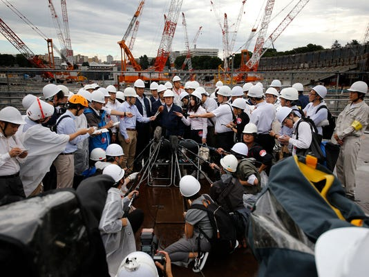 Japan's Tokyo Olympic minister Shunichi Suzuki, center, answer for reporter's question after inspect of a construction site of new national stadium in Tokyo, Tuesday, Sept. 12, 2017. Tokyo's main Olympic stadium is starting to take shape as structures of what will become spectator stands are being installed after 10 months of underground foundation work. (AP Photo/Shizuo Kambayashi)
