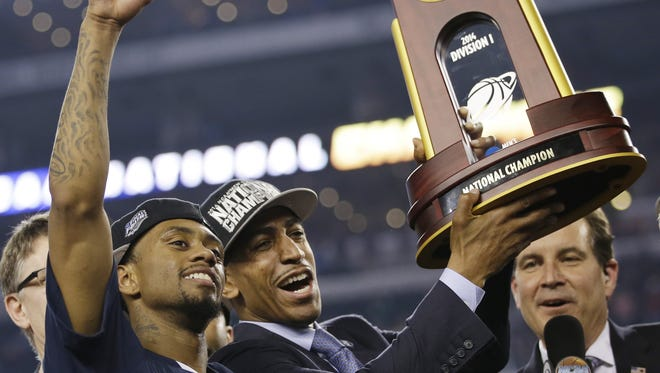 Connecticut head coach Kevin Ollie (center) celebrates the 2014 national title with his team.