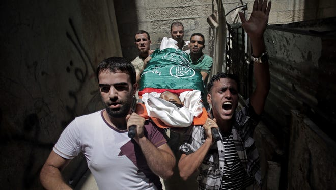 Palestinian relatives of Mohammed Naser, chant slogans as they carry his lifeless body to the family house during his funeral in the Khan Younis refugee camp in the southern Gaza Strip, Saturday, July 19, 2014. Naser and eight others were killed in an early morning Israeli missile strike, official said.
