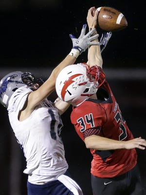 Seymour High School's Nick Fameree (34) knocks down a pass intended for Xavier's Bailey Headington during the second quarter of their Bay Conference game on Friday.