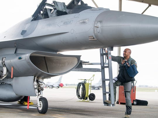 Major Rich Peace prepares to fly in his F-16 at the