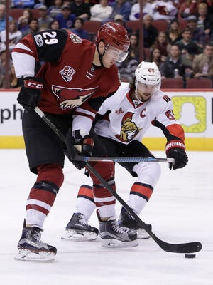 Arizona Coyotes left wing Brendan Perlini (29) and Ottawa Senators defenseman Erik Karlsson (65) battle for the puck during the second period of an NHL hockey game, Thursday, March 9, 2017, in Glendale, Ariz.
