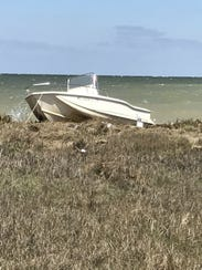 A 17-foot recreational fishing vessel sits aground