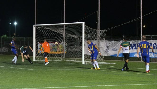 Kyle Legozzie scores for the University of Guam Tritons on an assist by Dylan Naputi against the Andersen Bombers in a Guam Football Association Budweiser Premier League playoffs match May 11 at the GFA National Training Center.