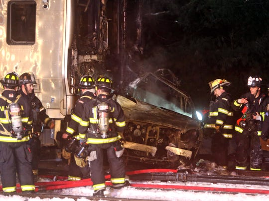 Firefighters examine the car that was struck by a Metro-North