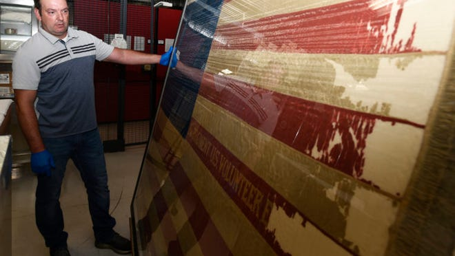 Scott Franklin, collection curator for the Engineer Museum, checks the condition of a U.S. flag dating back to the Spanish-American War June 4 during a month-long inventory of all artifacts housed at the John B. Mahaffey Museum Complex here.