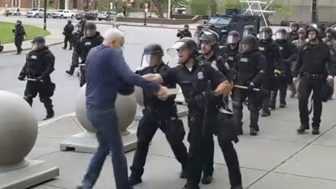 """In this image from video provided by WBFO, a Buffalo police officer appears to shove a man who walked up to police Thursday, June 4, 2020, in Buffalo, N.Y. Video from WBFO shows the man appearing to hit his head on the pavement, with blood leaking out as officers walk past to clear Niagara Square. Buffalo police initially said in a statement that a person """"was injured when he tripped & fell,†WIVB-TV reported, but Capt. Jeff Rinaldo later told the TV station that an internal affairs investigation was opened. Police Commissioner Byron Lockwood suspended two officers late Thursday, the mayor's statement said."""