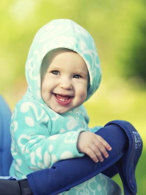 happy baby smiling with blue hood in stroller for  walk