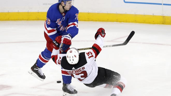 Rangers defenseman Brady Skjei knocks Devils center Nico Hischier to the ice.