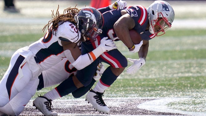 Denver Broncos linebacker Alexander Johnson, left, tackles New England Patriots running back Damien Harris in the first half of their game, Sunday, Oct. 18, 2020, in Foxboro.
