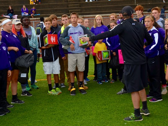 Glen Este soccer players prepare to present soccer balls to the Withrow soccer team.