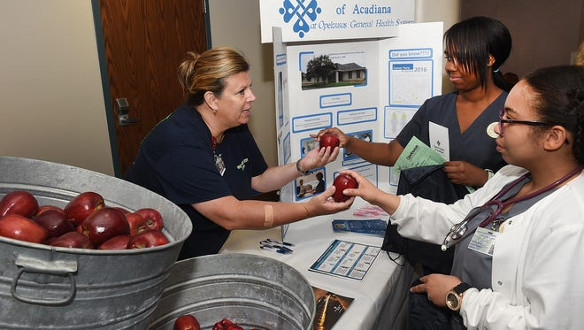 """""""An apple a day keeps the doctor away"""" said Renee Fontenot, Cancer Center of Acadiana at Opelousas General Health System as she hands out apples at the annual  Opelousas General Health System Health Fair last year. The fair returns this weekend."""