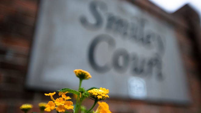 Flowers grow in front of the Smiley Court sign on Tuesday, June 6, 2017, in Montgomery, Ala.