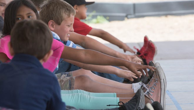 Student in the Mesilla Elementary School Run Club touch their toes as part of a warm up on Wednesday, March 29, 2017, during the last day of Run Club before the Tumbleweed Run this weekend.