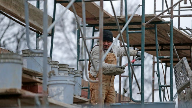 A worker lays bricks for a new wall at the rebuilt BP gas station.