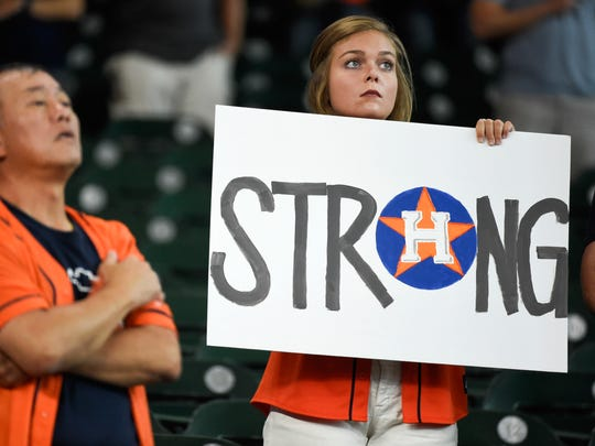 A fan holds a sign during the national anthem before