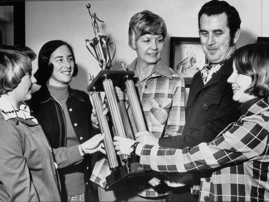 FILE – Pat Roy (center) hold the IHSAA trophy for the
