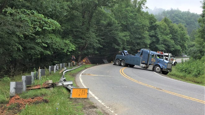 The truck container carrying fireworks is lifted out of the forest edge.