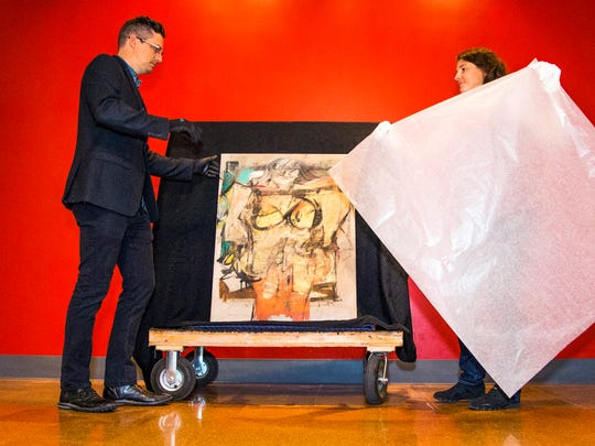"""Nathan Saxton, exhibition specialist, left, and Kristen Schmidt, registrar, wrap up """"Woman-Ochre,"""" a painting by Willem de Kooning, at the University of Arizona Museum of Art on Aug. 10, 2017. The painting has been returned to the museum, 31 years after it was stolen in a brazen heist."""
