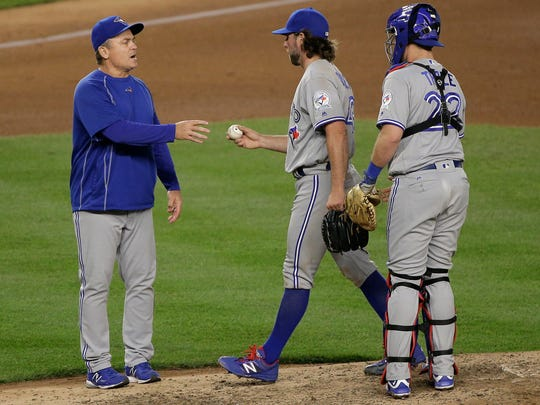 Toronto Blue Jays pitcher R.A. Dickey, center, is removed by manager John Gibbons as catcher Josh Thole watches during the seventh inning of a baseball game against the New York Yankees, Tuesday, May 24, 2016, in New York. (AP Photo/Julie Jacobson)