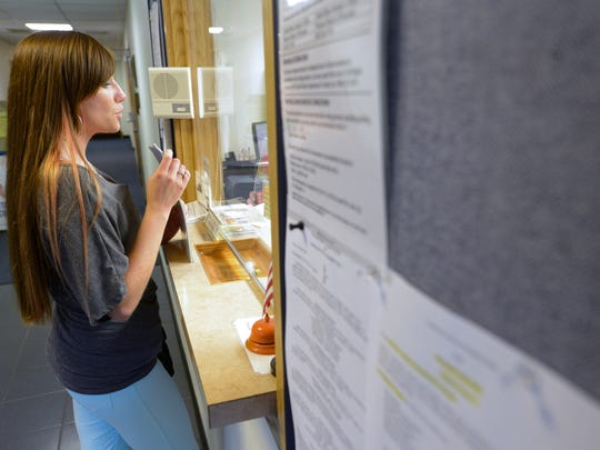 Cassie Nygren asks a receptionist about posting a flier with statistics about heroin and opioid use, part of her work Rise Together, in the Marinette Police Station distributes fliers from Rise Together in Marinette on Thursday, Aug. 7.