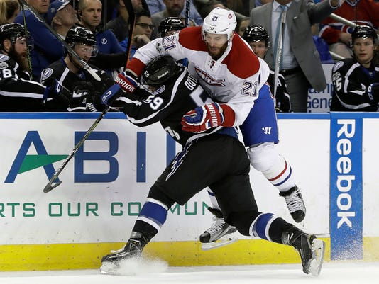 Montreal Canadiens left wing Dwight King (21) avoids a check by Tampa Bay Lightning defenseman Jake Dotchin (59) during the first period of an NHL hockey game Saturday, April 1, 2017, in Tampa, Fla. (AP Photo/Chris O'Meara)