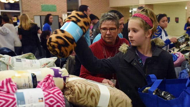 Nadia Hendershot, right, picks out a blanket at the Chillicothe City Schools' Community Night Tuesday in the Chillicothe Middle/High School cafeteria. The event included free food, clothing, blankets, haircuts and more.