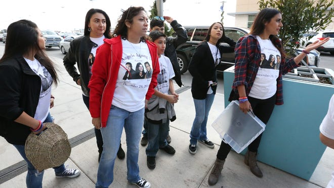 Denise Ramirez, right, and other friends and family members of Joshua Deal, his brother, Isaiah Deal, and Shannon Del Rio give out candy canes with a message about safety Wednesday outside the Fountains at Farah. The Deal brothers and Del Rio were killed in a traffic accident in the early morning hours of Dec. 24, 2014. The group of about 20, who wore T-shirts with pictures of the three victims, gave out more than 600 candy canes to shoppers with a message urging them to not drink and drive.