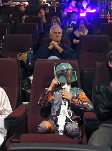 Star Wars fans Sailor Durbin, 10,left,  her brothers, Stellar, 7, Sage, 16, are seated and waiting to see the first showing of Star Wars: The Force Awakens at Harkins Tempe Marketplace on December 16, 2015.