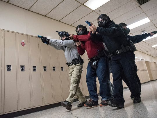Officers run a scenario of a possible shooter, moving