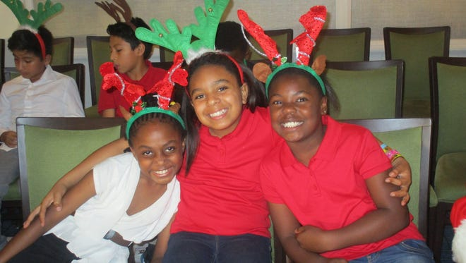 Each year, volunteers help to make the holidays more manageable and bright for at-risk families served by the Edna W. Runner Tutorial Center in Jupiter. Pictured, from left, are Juliete, Makayla and Juliette, who are enrolled in the after school program.