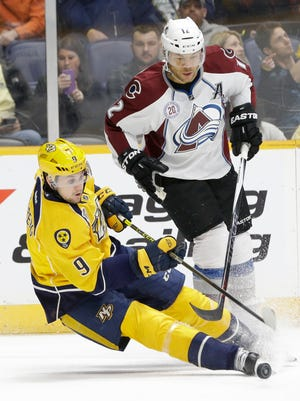 Nashville Predators center Filip Forsberg (9), of Sweden, falls as he battles Colorado Avalanche right wing Jarome Iginla (12) for the puck in the second period Saturday, Dec. 12, 2015, in Nashville. Iginla was called for hooking on the play.
