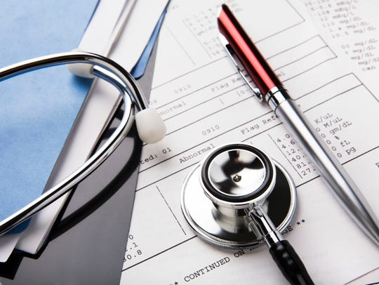 Stethoscope and pen resting on a sheet of medical lab