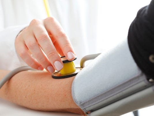 A nurse checking a patients blood pressure