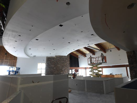 Painters go up a cherry picker to paint the ceiling of the Crossroads Tavern and Grill at The Summit entertainment center in Windsor July 16, 2014.