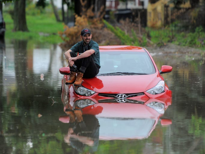 Paul Candela of Grosse Pointe Woods sits on the hood