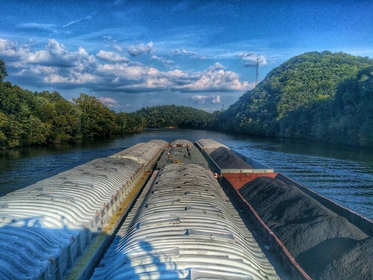 A daytime river scene captured from the wheelhouse of an Ingram Barge Co. towboat