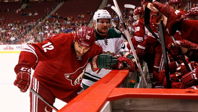 Paul Bissonnette takes away the stick of Minnesota Wild's Matt Cooke and then throws it into the Coyotes bench in the 2nd period during NHL hockey action in Glendale.